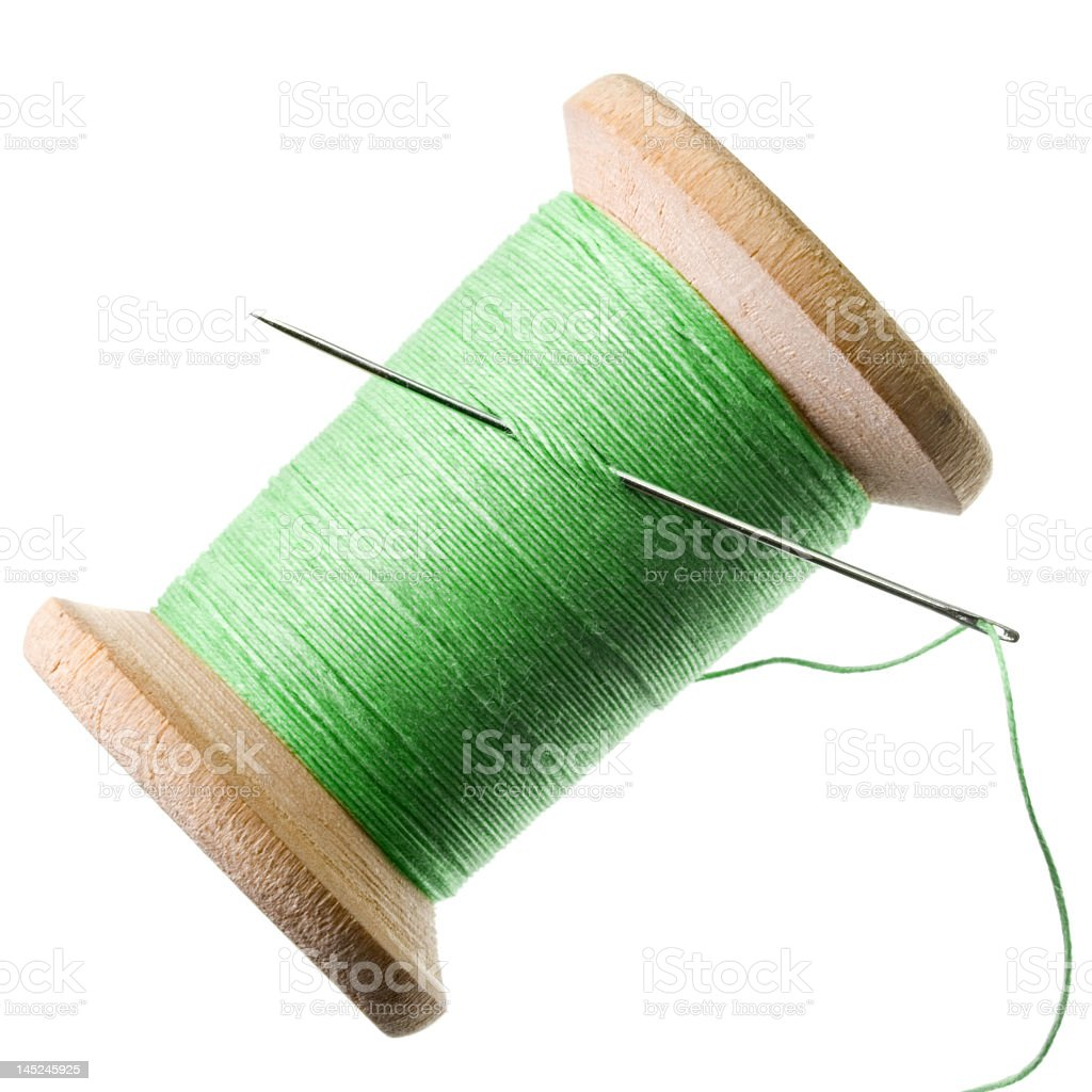 Green thread on a spool with a needle threaded royalty-free stock photo