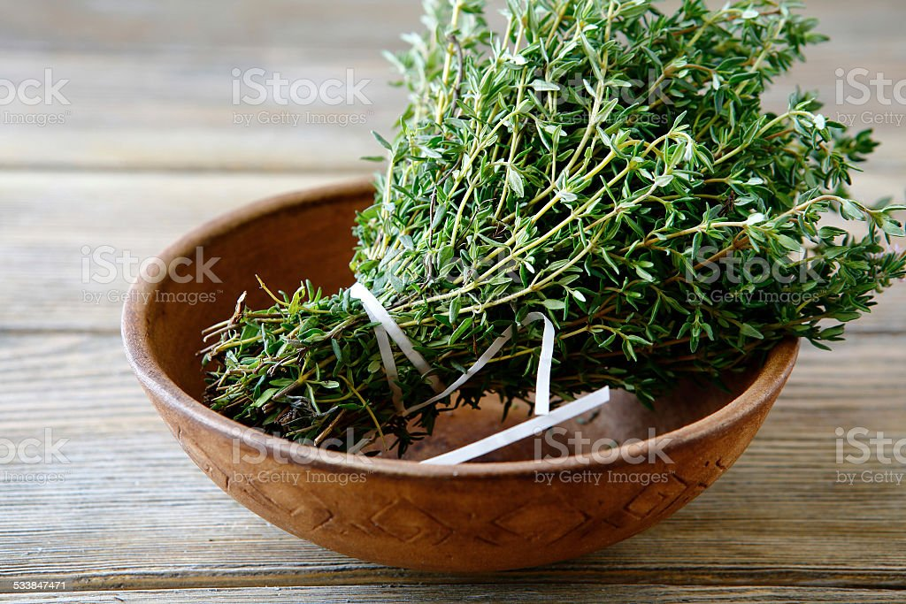 Green thyme in a bowl on boards stock photo