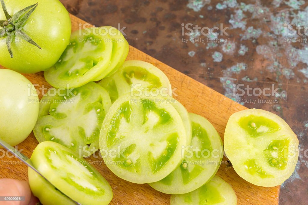 green tomatoes on a cutting board stock photo