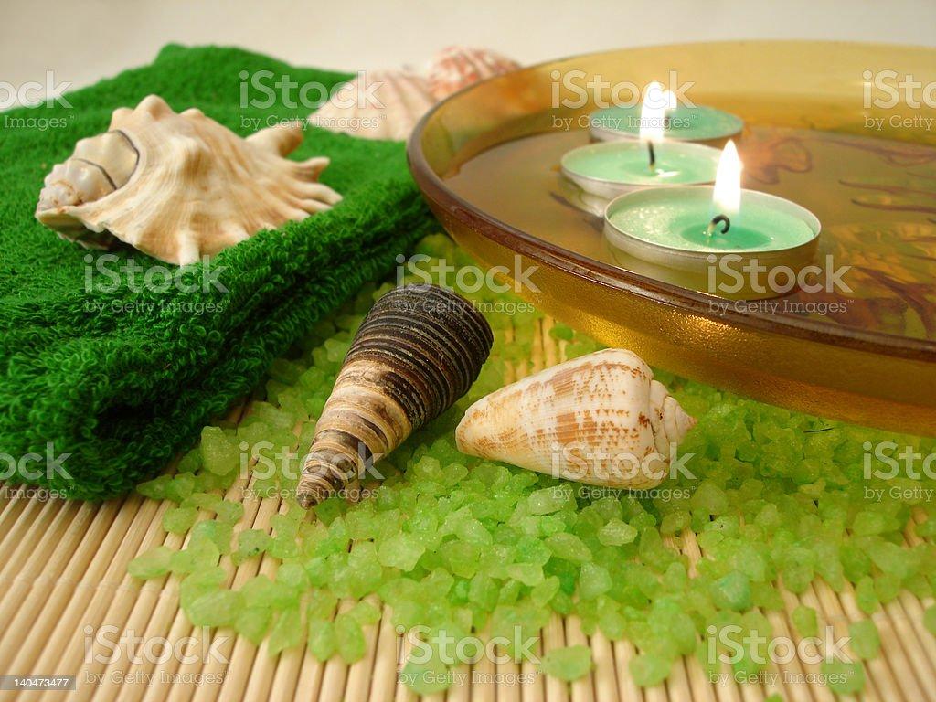 Verde de cozinha, conchas, velas no prato com água e sal foto de stock royalty-free