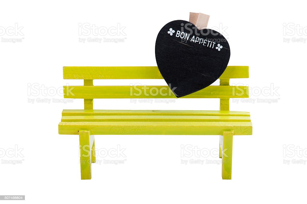 Green toy bench and yellow heart stock photo