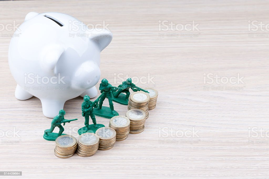 Green toy soldiers in front of piggy bank stock photo