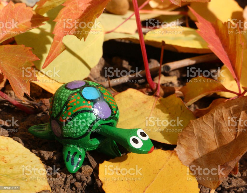 Green toy turtle in yellow and orange autumn leaves stock photo