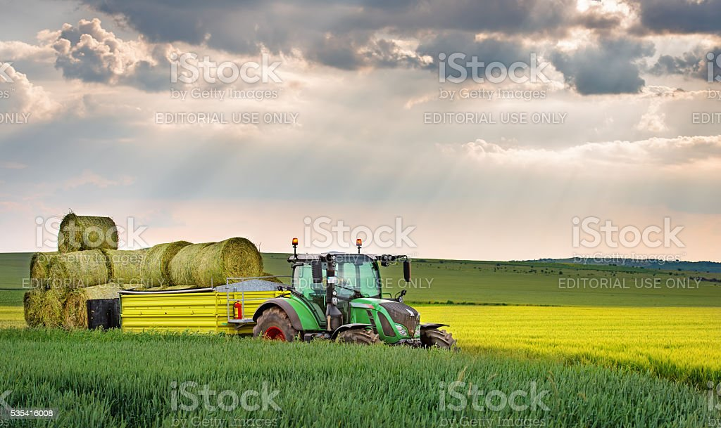 green tractor and dramatic sky. stock photo