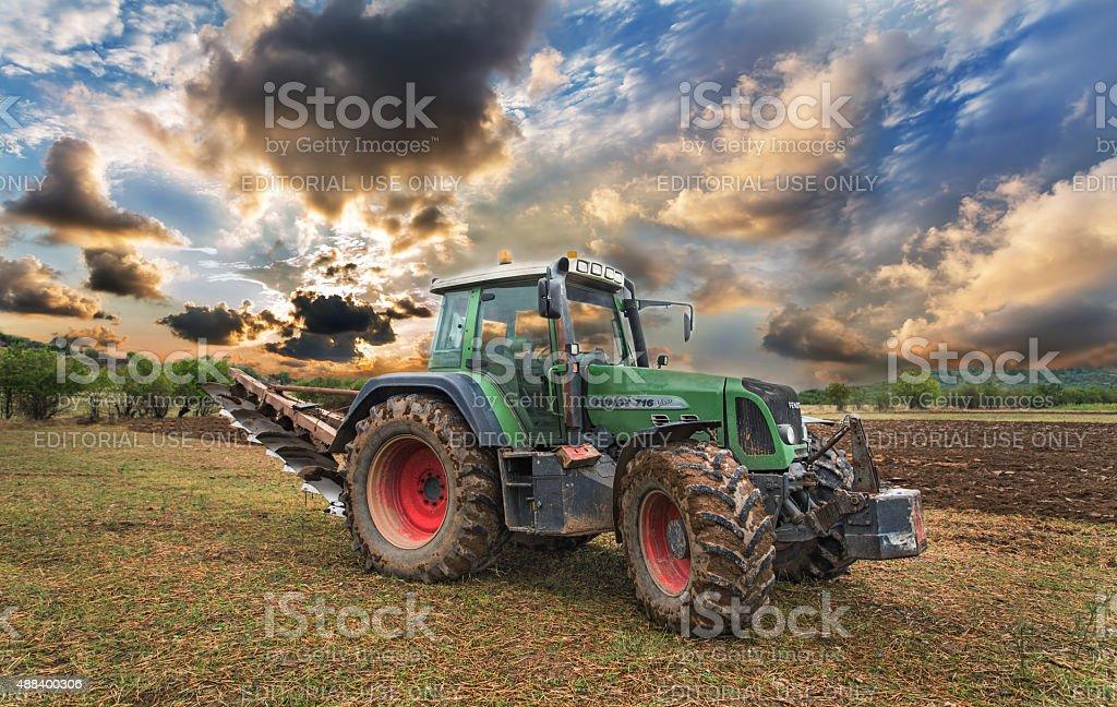 Green tractor on golden sunset sky. stock photo