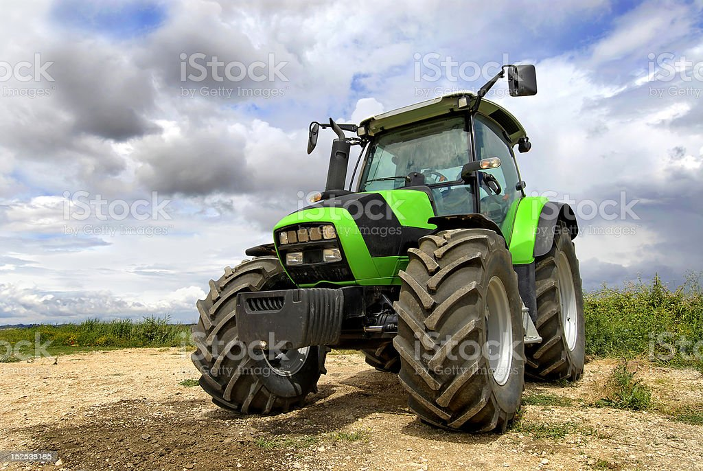 A green tractor under looming gray clouds outside royalty-free stock photo
