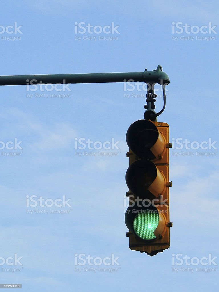green traffic light against blue sky stock photo