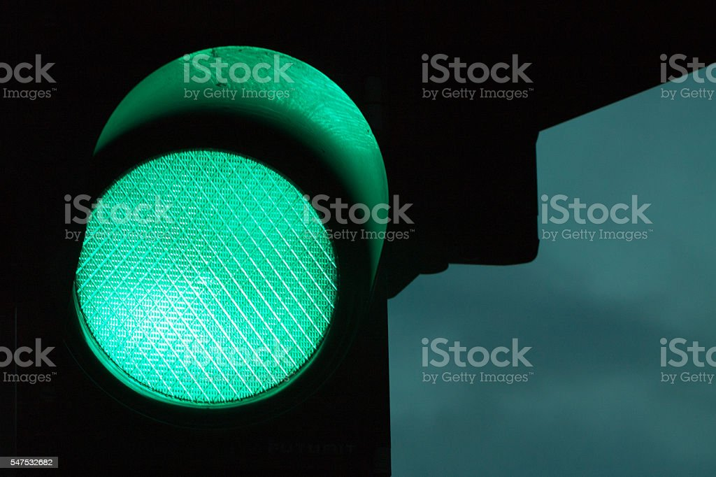 Green traffic light by night and dark sky at the stock photo