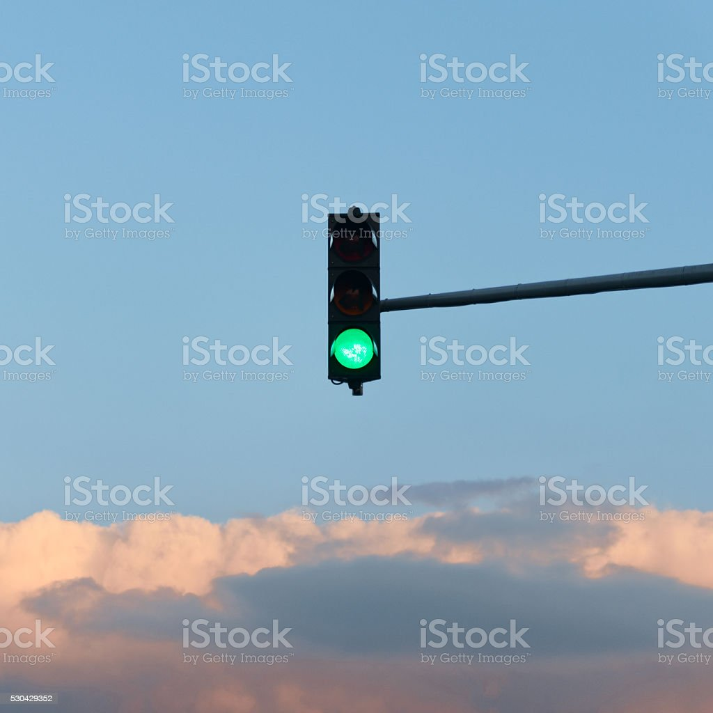Green traffic light on the blue sky stock photo