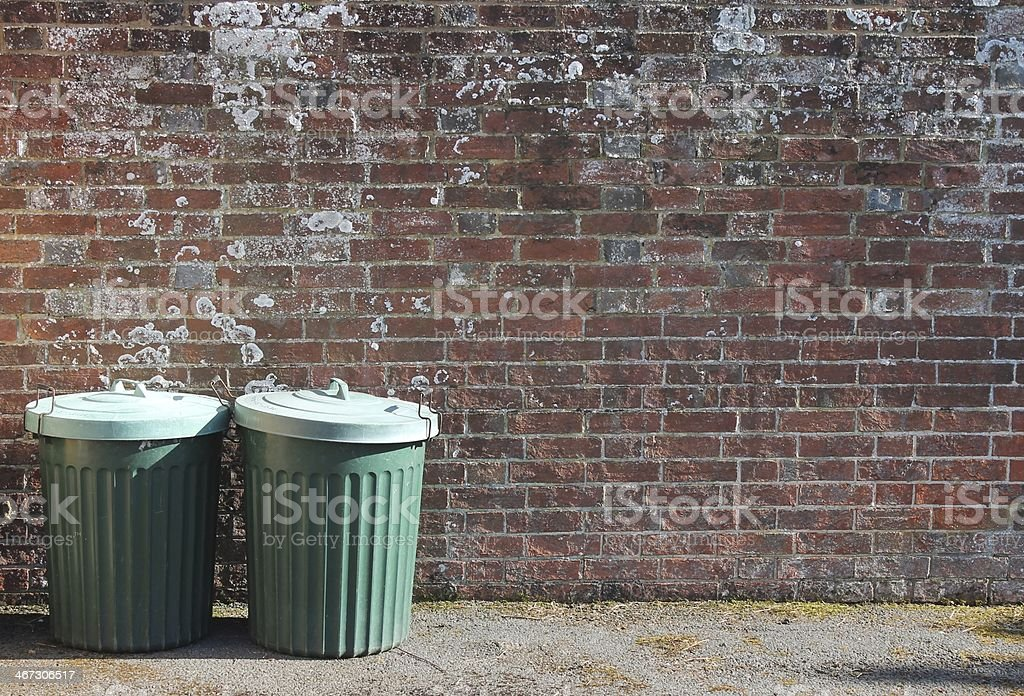 Green trash can dustbins outside street by brick wall stock photo