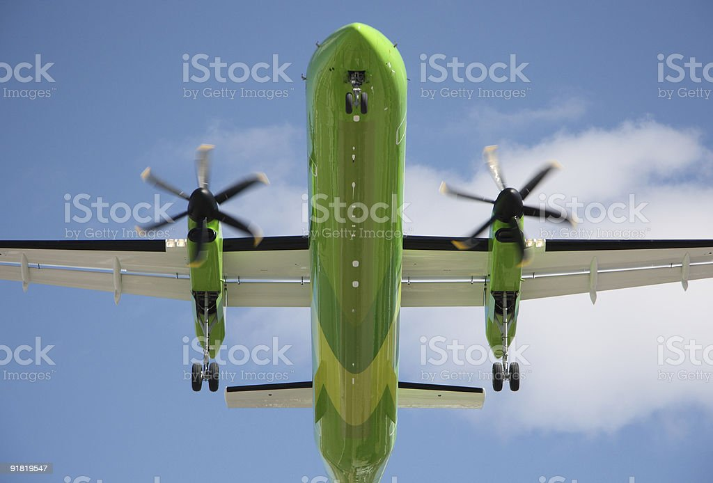 Green turboprop airplane on landing approach royalty-free stock photo