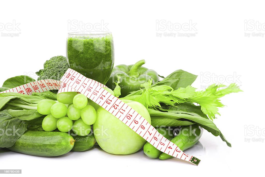 Green Vegetable juice and tape measure isolated on white background royalty-free stock photo