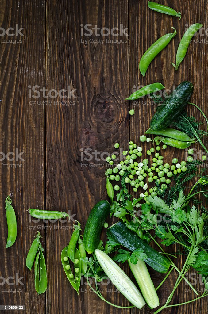 Green vegetables on wooden background peas, parsley, cucumber, dill stock photo