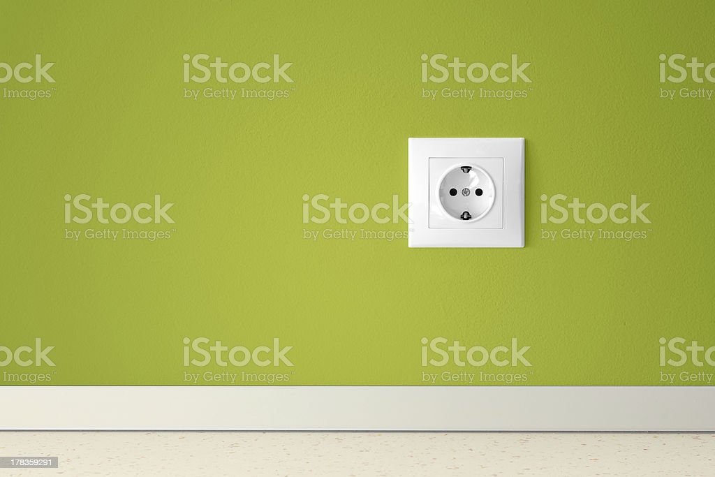 Green wall with european electric outlet stock photo