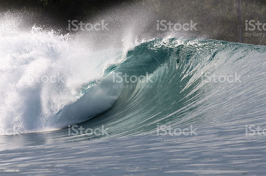 green wave breaking with offshore wind in indonesia stock photo
