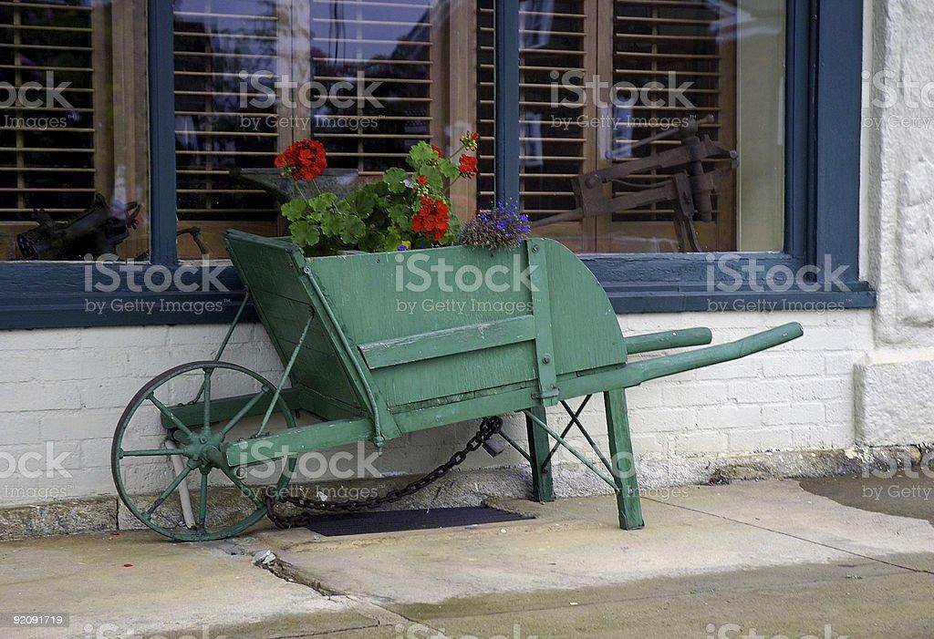 green wheel barrow with flowers royalty-free stock photo
