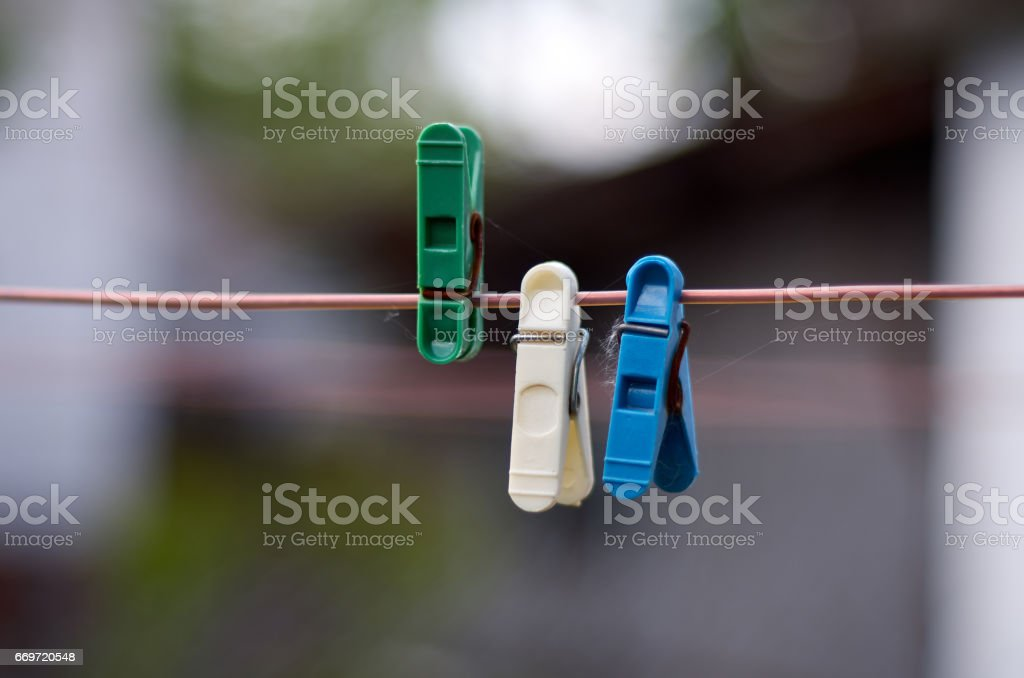 Green, white, blue clothes peg on a washing line stock photo