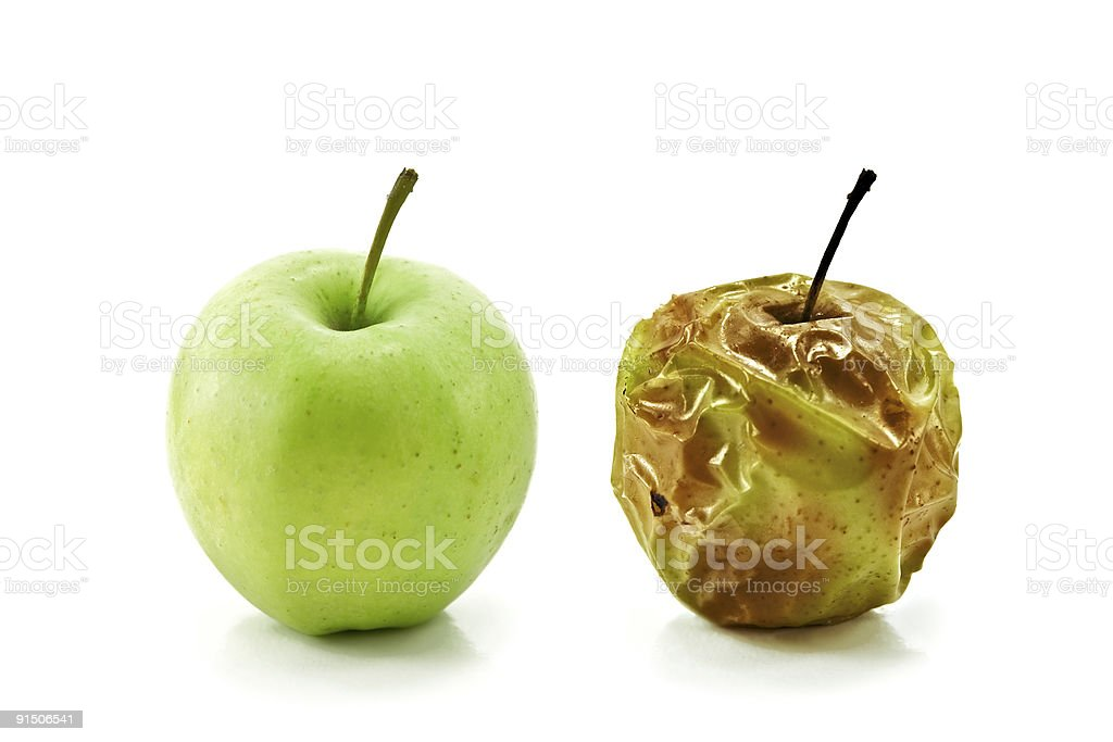 Green whole apple next to rotten apple stock photo