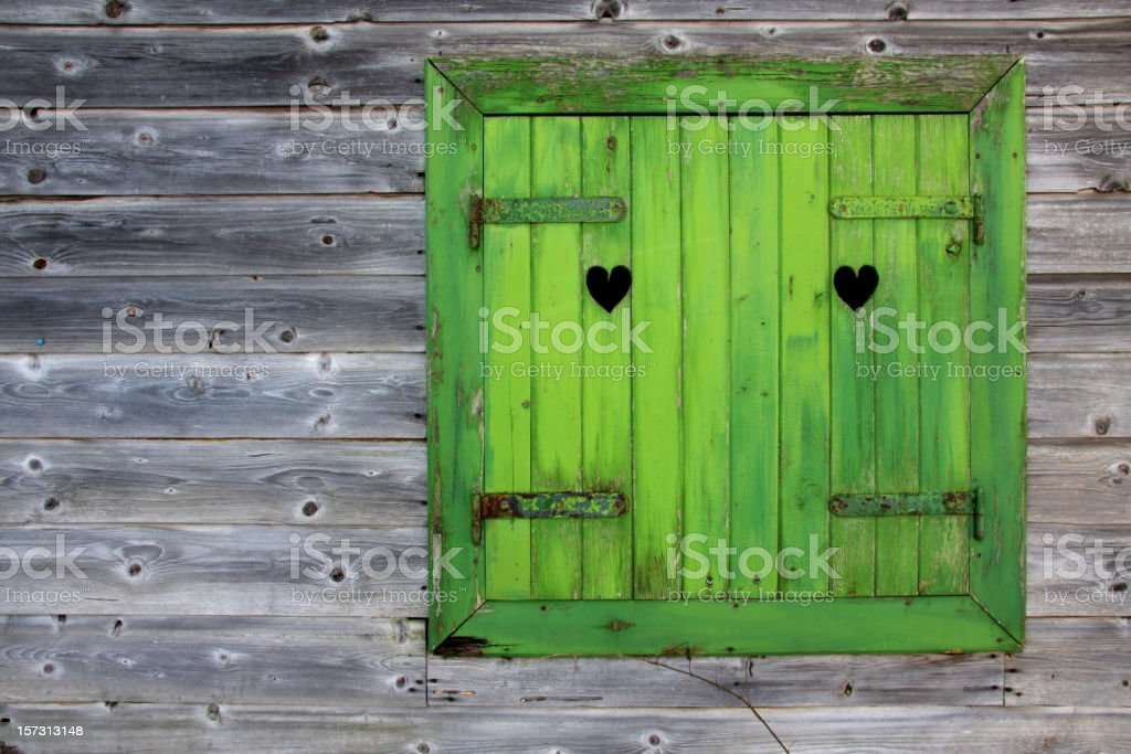 Green window of a wooden hut in the Alps stock photo