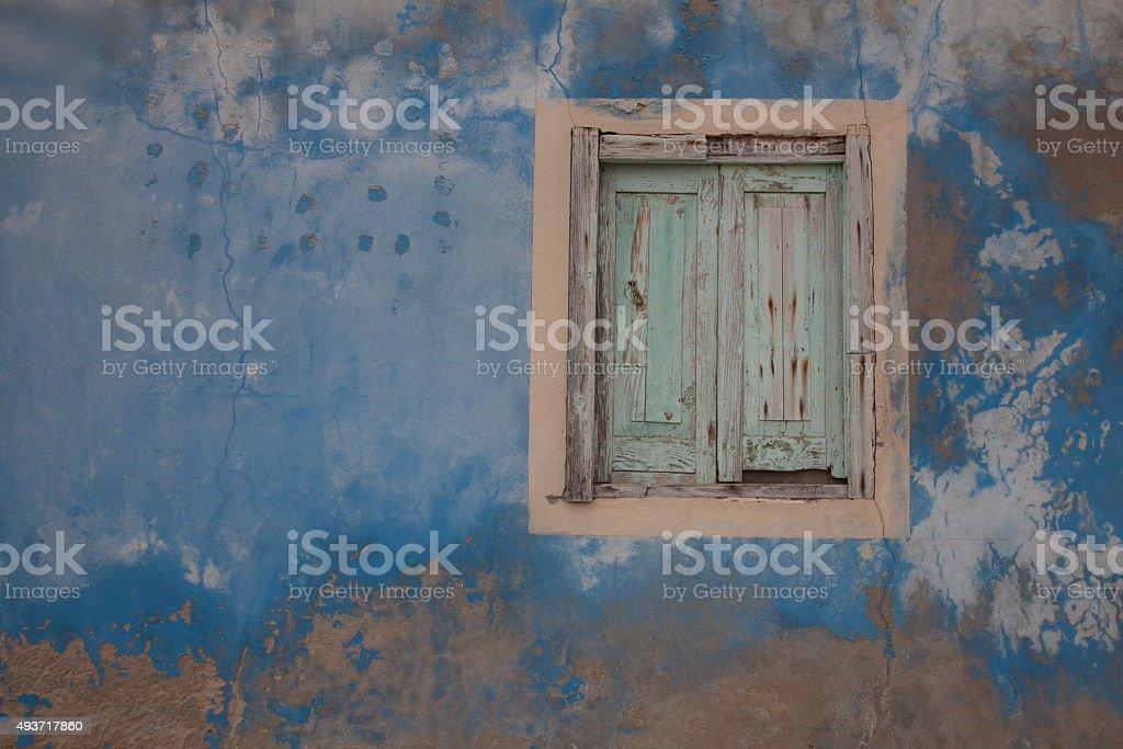 Verde finestra con persiane centre destra sulla parete blu foto stock royalty-free
