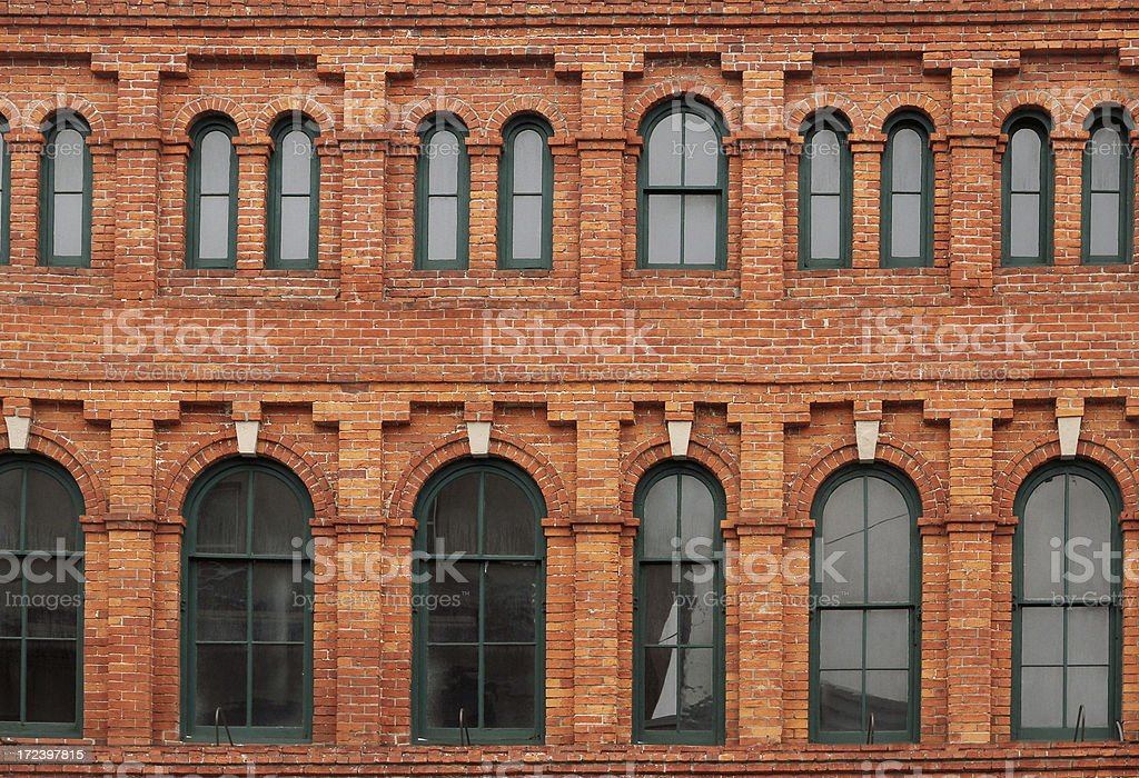 Green windows in a red brick wall royalty-free stock photo