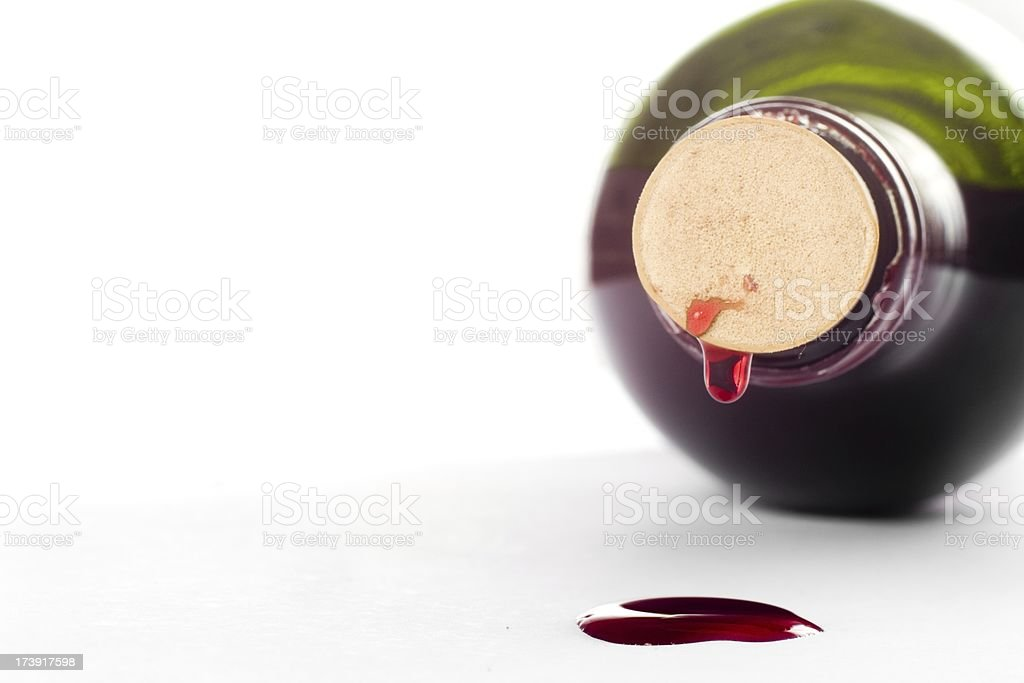 Green wine bottle lying down with red drops on white stock photo