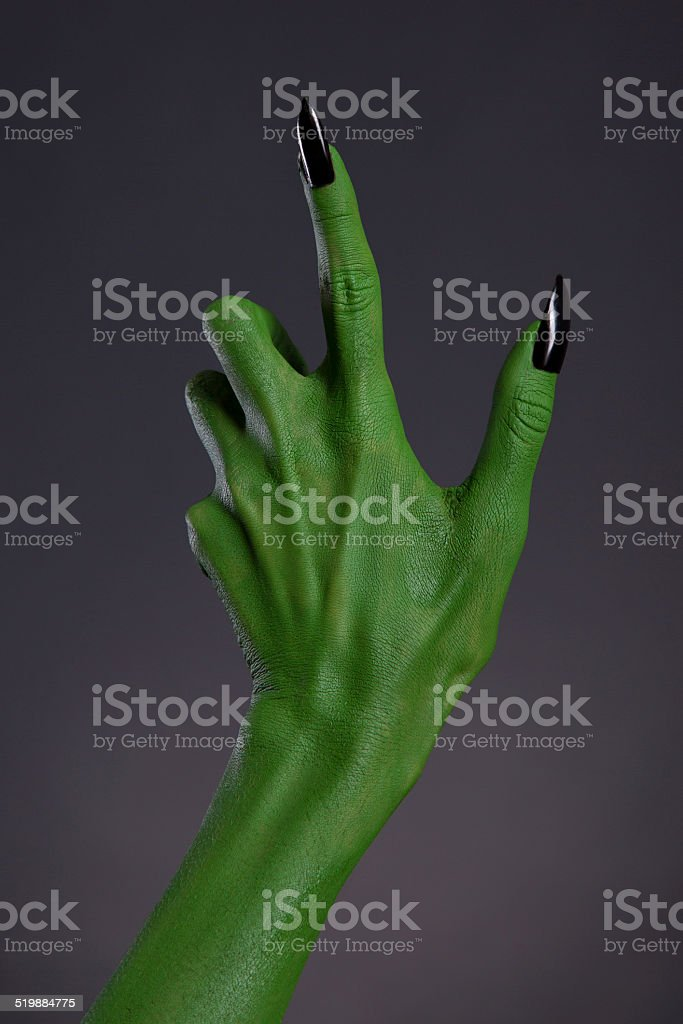 Green witch hand with black nails, real body-art stock photo