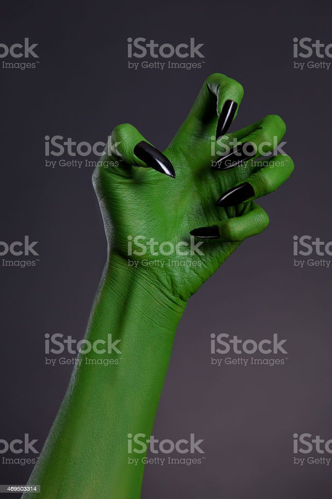 Green witch hand with sharp black nails, real body-art stock photo