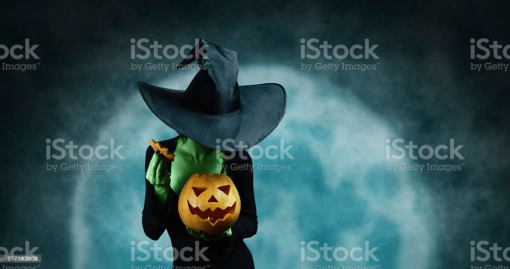 Green witch with pumpkin stock photo