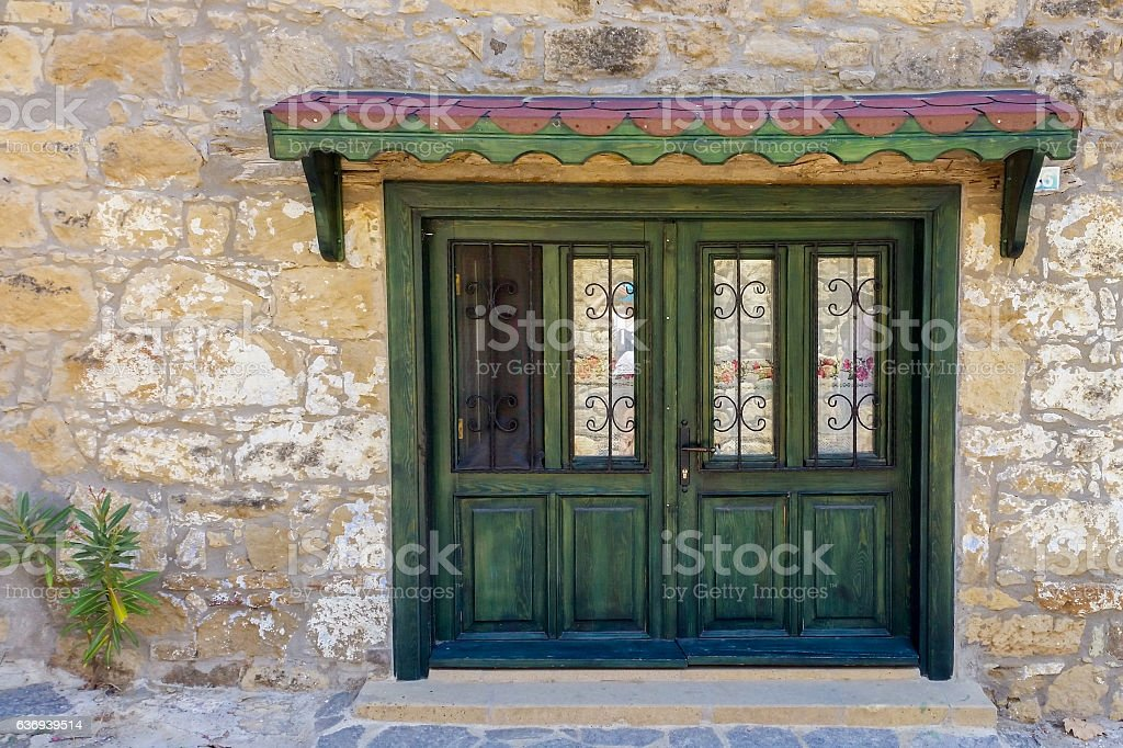 Green wooden door with wrought iron of a stone building stock photo