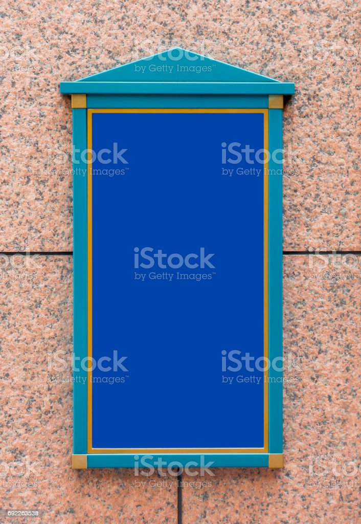 Green wooden signage on Red stone wall with blue copy space stock photo