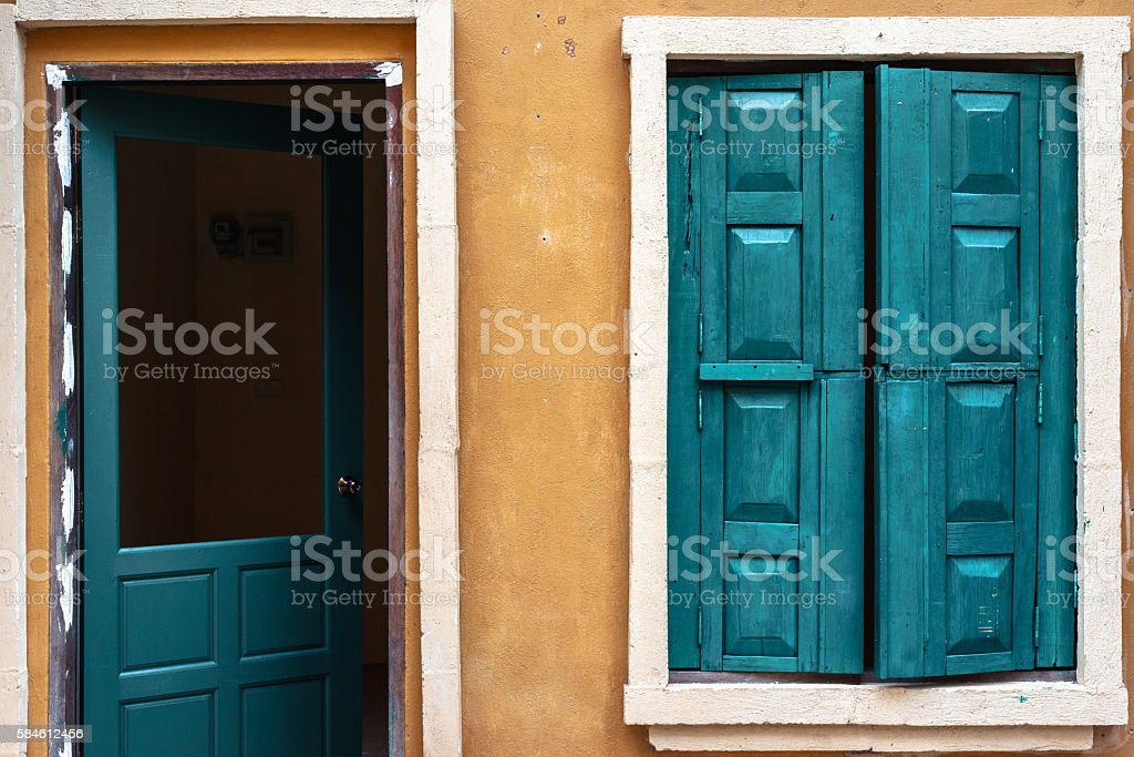 Green wooden window and door on yellow wall photo libre de droits