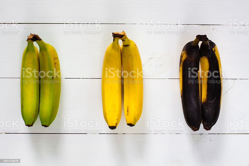 Green, yellow and black bananas. stock photo