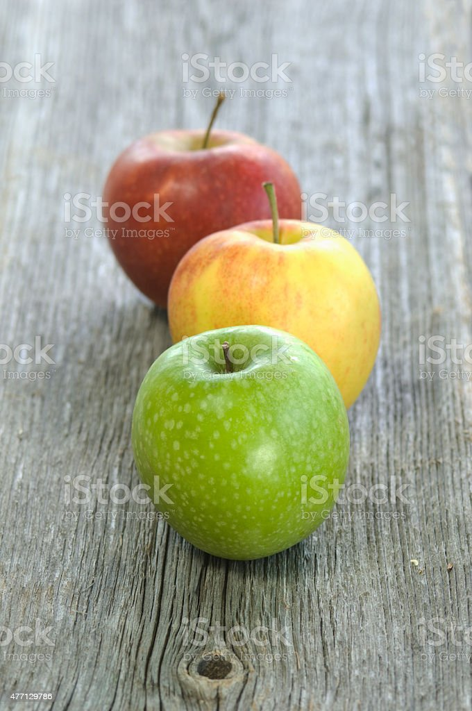 Green, yellow and red apple in a row on wood stock photo