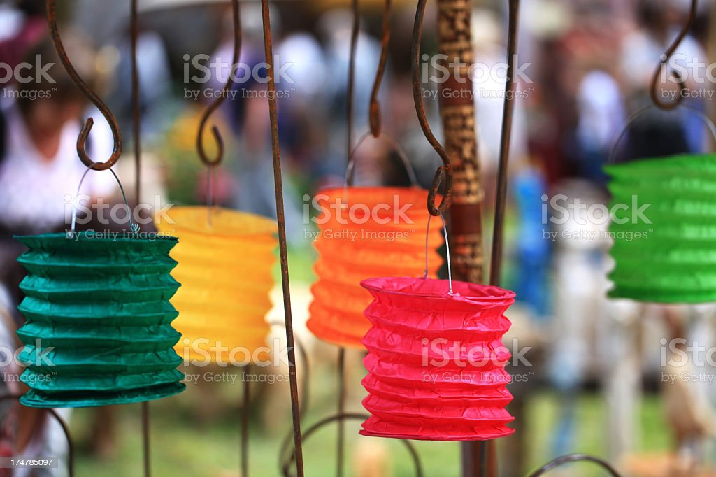 Green yellow red and orange paper lanterns hanging on metal stock photo