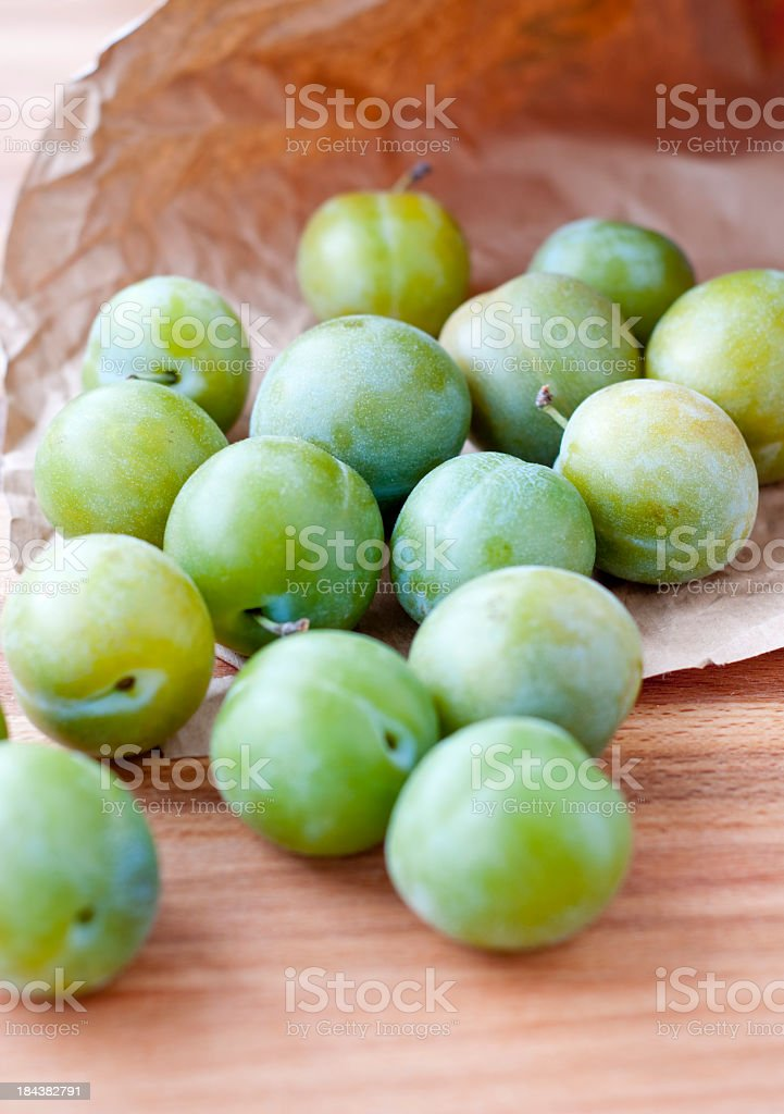 Greengages rolling out of a paper bag stock photo