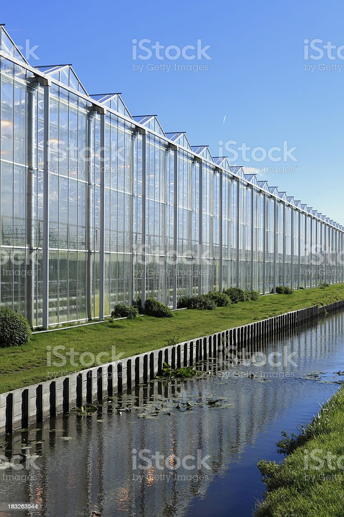 greenhouse and its reflection in the water stock photo