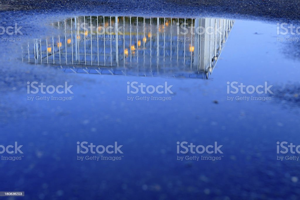 greenhouse reflected in a pool of water stock photo
