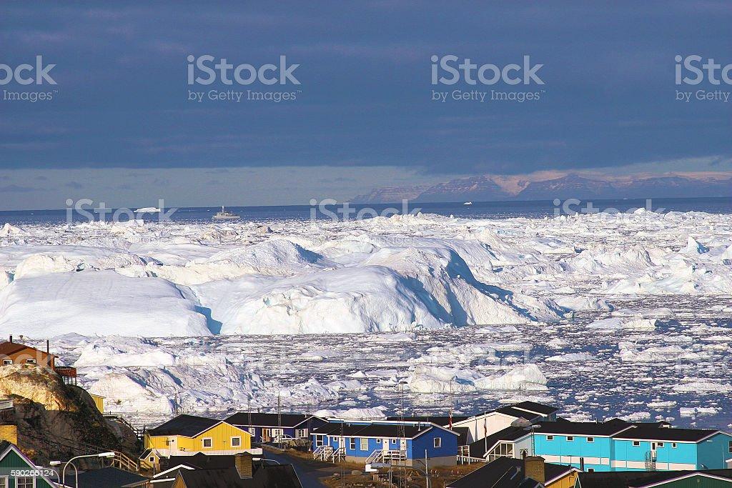 Greenland glacier glaciers houses ocean small town burg sky stock photo