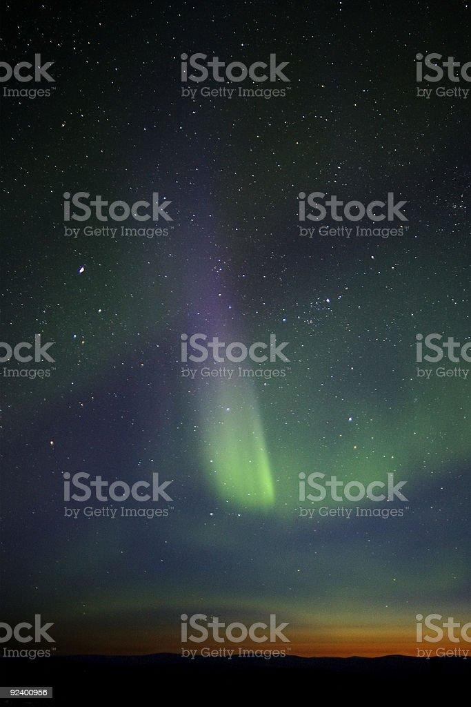 Green-purple streak of aurora over twilight horizon. Many stars royalty-free stock photo