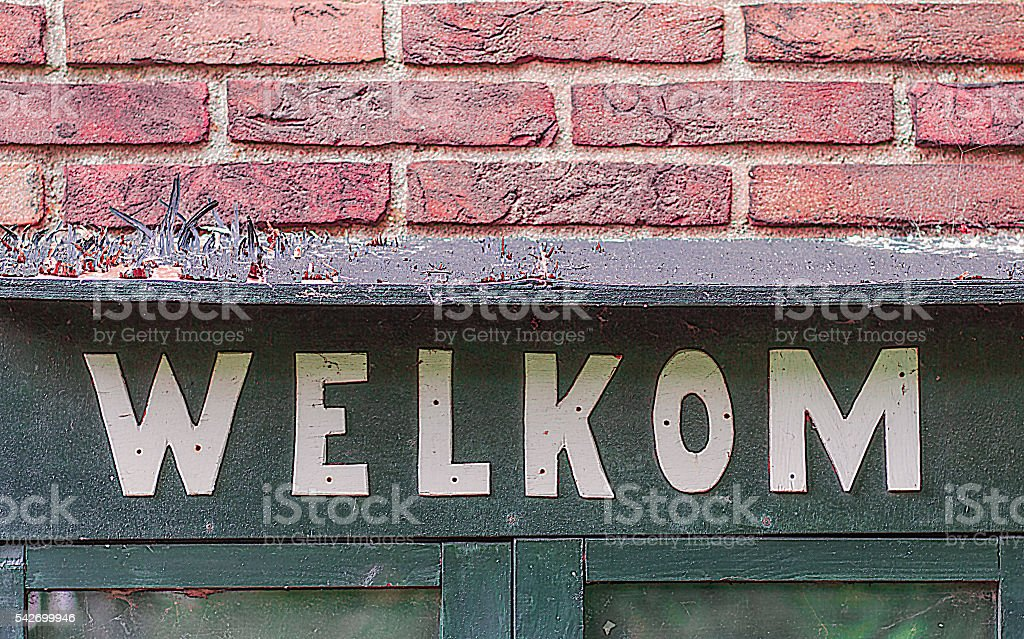 Greeting at the entrance on a brick wall stock photo