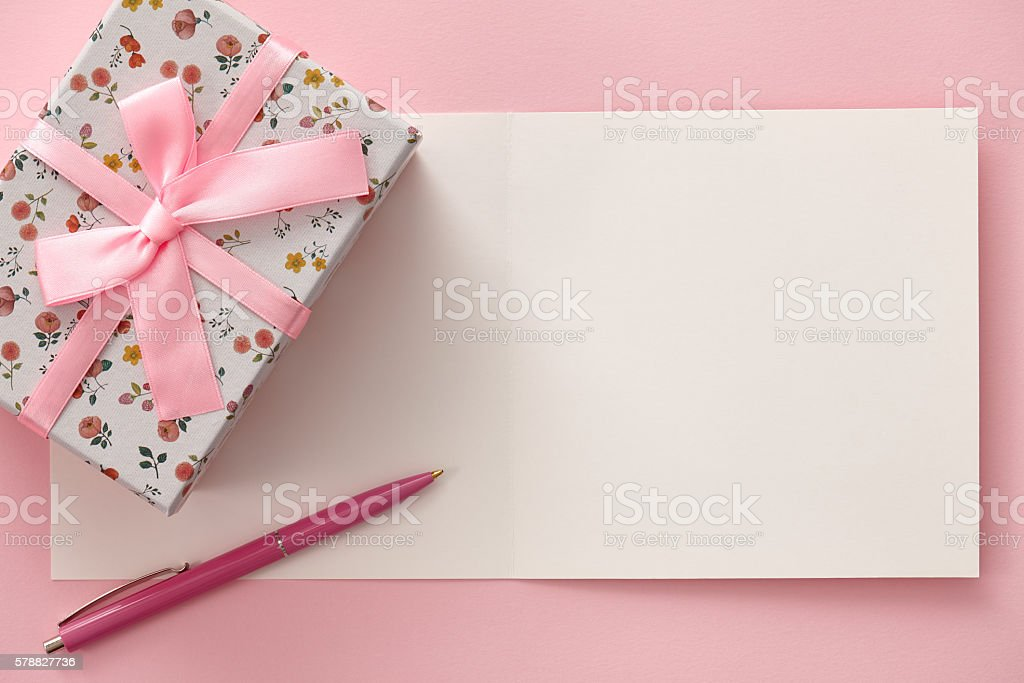 Greeting card, gift box and pen in pink colors stock photo