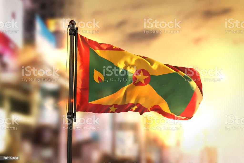 Grenada Flag Against City Blurred Background At Sunrise Backlight stock photo