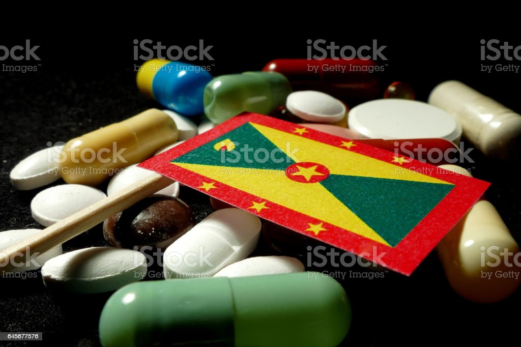 Grenada flag with lot of medical pills isolated stock photo