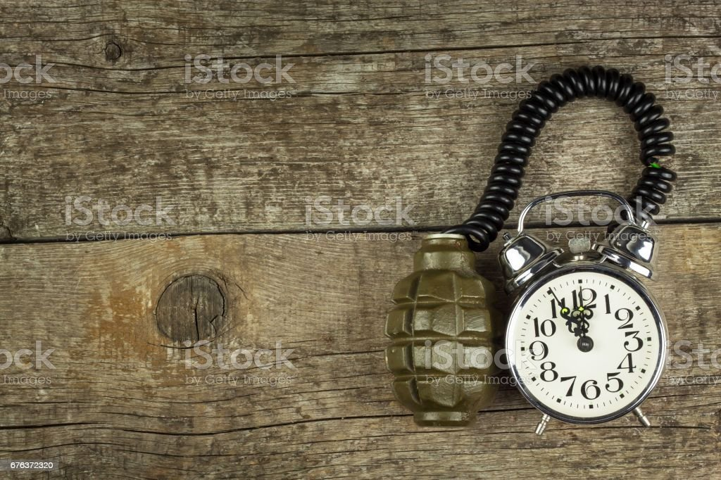 Grenade and old alarm clock. Timed bomb stock photo