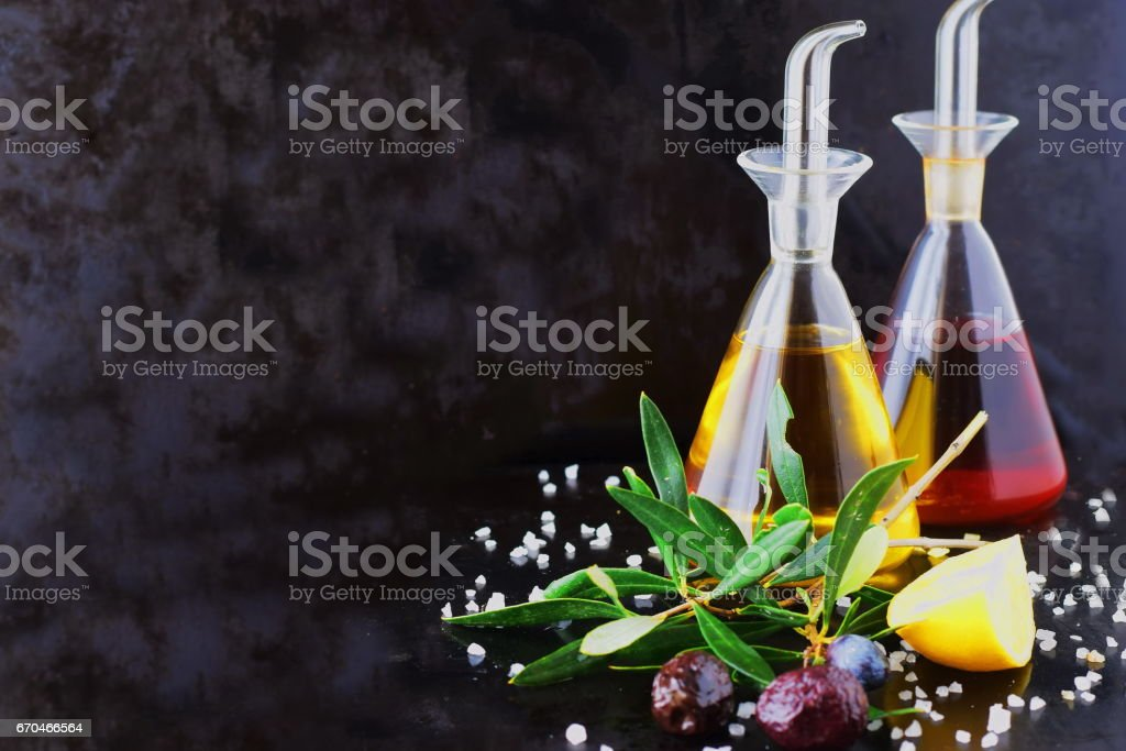Grey abstract background with olive oil and wine vinegar glass jars with lemon, sea salt, garlic and olive branch. Space for text. stock photo