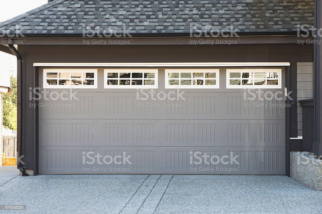 Grey and white garage door with windows stock photo