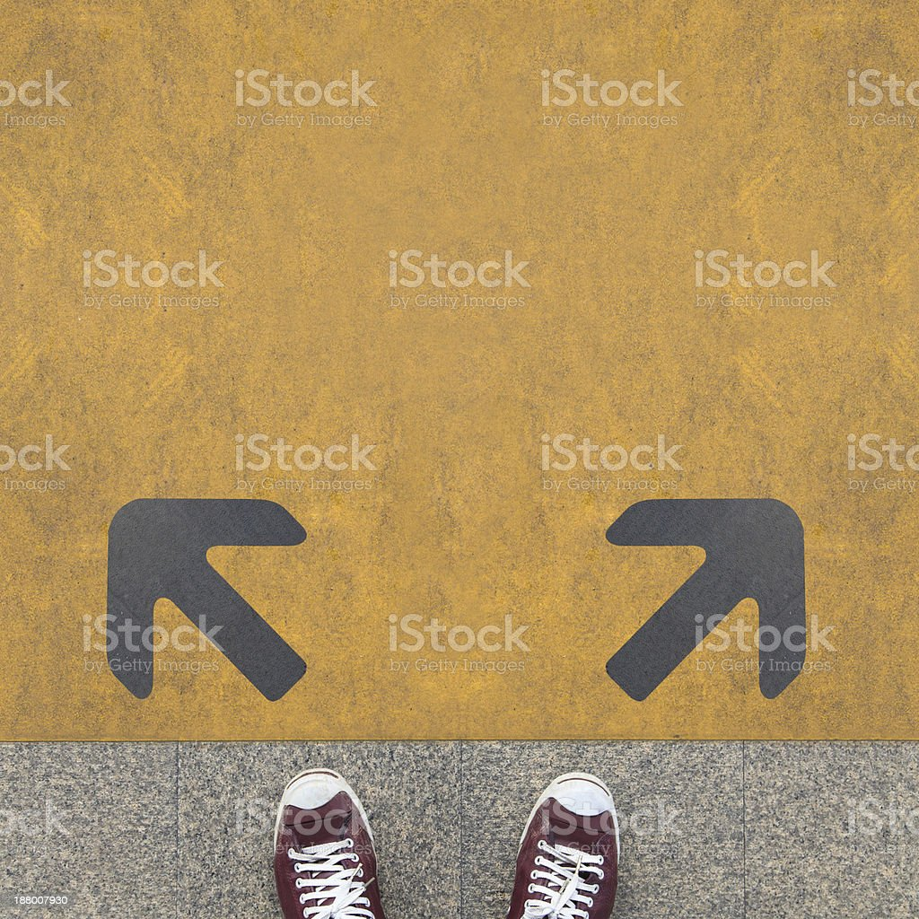 Grey arrows on a yellow ground with a pair of sneakers stock photo