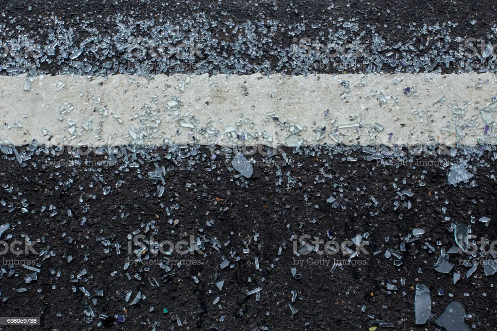 Grey background created from picture of pieces of broken glass on asphalt concrete road. stock photo