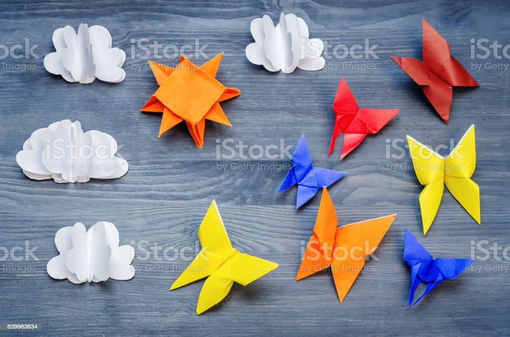 Grey background with paper multicolored butterflies, sun and clouds stock photo